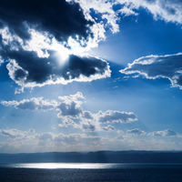 sunlight passes through dark clouds over Dead Sea