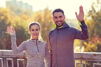 smiling couple waving hand outdoors