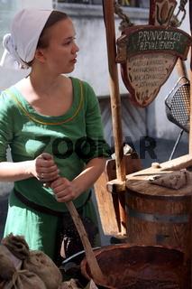 Eine Mittelalterlich angezogene Frau in einer Gasse der Altstadt von Tallinn der Hauptstadt von Estland
