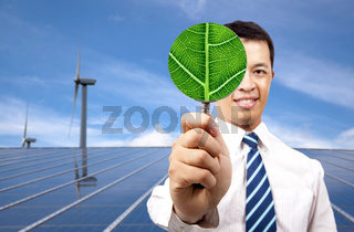green energy business concept.young businessman holding Magnifier and standing in front of solar panel and wind turbine