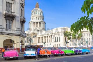 Farbenfrohe amerikanische Oldtimer parken aufgereiht vor dem Capitolio in Havanna City Kuba