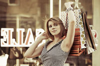 Happy young woman with shopping bags against mall window