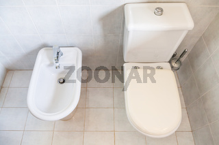 white toilet with bowl drain and bidet