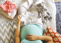 Pregnant woman is packing baby clothes