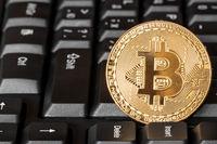 One golden bitcoin on keyboard