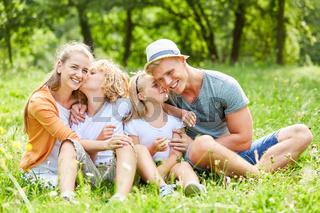 Glückliche Familie sitzt entspannt im Garten
