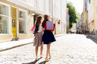 happy women with shopping bags walking in city