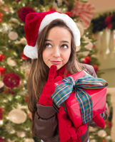 Thinking Girl Wearing A Christmas Santa Hat with Bow Wrapped Gift In Front of Decorated Tree