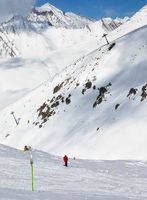 Skier on snowy ski trace and mountains in clouds