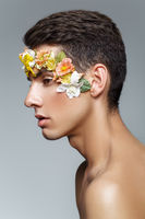 handsome young man with flowers on face