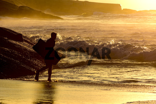 Bodyboarder at sunrise