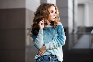 Happy young fashion woman with long curly hairs on city street