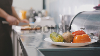 Chief on the kitchen of restaurant cuts vegetables for salad - cooking concept, de-focused