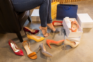 young woman trying and choosing shoes at store