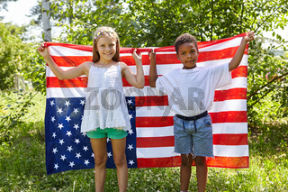 Zwei Kinder halten eine amerikanische Flagge