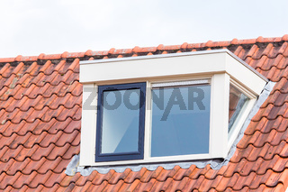 Dormer window on  roof of attic with roof tiles