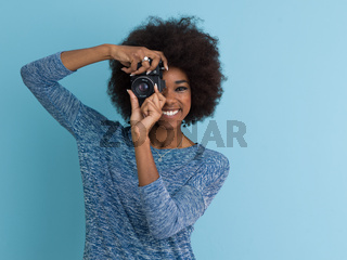 african american girl taking photo on a retro camera