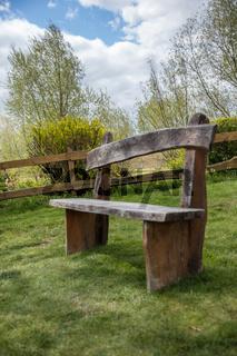 Sitzbank aus Holz im Garten auf Wiese