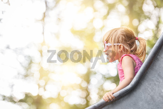Happy blond girl on a slide