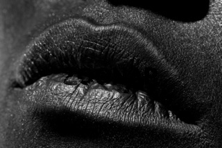 The lips of a young girl covered with black paint