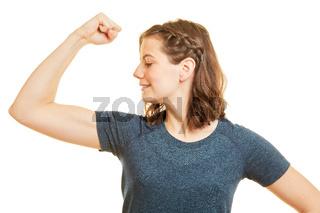 Sportliche Frau schaut auf angespannten Bizeps Muskel