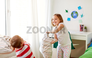 kids playing and fighting by pillows at home