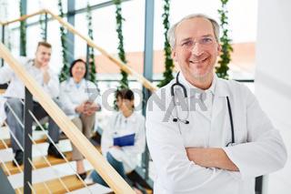 Senior als erfolgreicher Chefarzt vor seinem Team