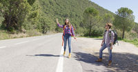 Young travellers hitch hiking on road