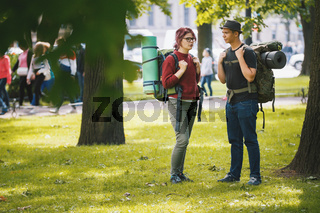 Teenagers tourists with backpacks have conversation in the park at summer midday