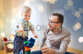 father and son playing with toy blocks at home