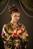 Schöne junge Frau als Geisha mit Kerze