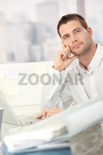 Daydreaming young man sitting at desk