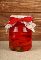 Jar of pickled red hot chili peppers on table