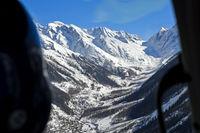Blick aus einem Helikopter über das Lötschental auf die schneebedeckten Berner Alpen