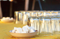 Two plates containing sugar cubes and several upside down glasses on a table