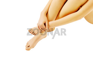 Young naked woman sitting on the floor and touching her foot