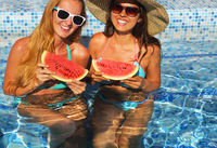 Two sexy women with dark hair eating watermelon