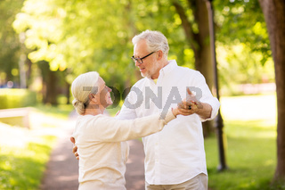 happy senior couple dancing at summer park