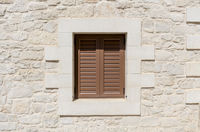 window with brown shutter and a natural stone wall