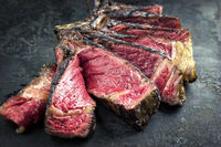 Barbecue dry aged Wagyu Tomahawk Steak sliced as close-up on old metal sheet