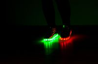 Fashionable sneakers with LED lighting on the legs of a girl with red and green colors