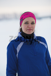 Portrait of a young female sportswoman in winter ice river