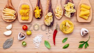 Italian cuisine concept .Various kind of pasta in wooden spoons with ingredients sweet basil ,tomato ,garlic ,parsley ,bay leaves ,pepper ,champignon and parmesan cheese on bamboo cutting board.