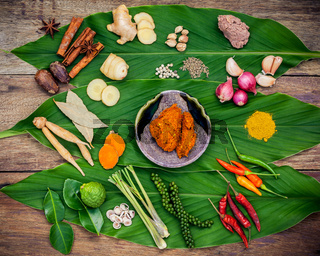 Various of Thai food Cooking ingredients and spice red curry paste ingredient of thai popular food on turmeric leaf background. Spices ingredients chili ,pepper, garlic and Kaffir lime leaves .