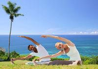 happy couple making yoga exercises outdoors