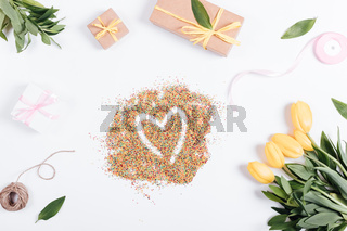 Tulips, boxes with gifts and ribbons around the candy in heart shape