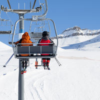 Two skiers on chair-lift and snowy ski slope