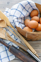 Brown eggs in old sieve,rolling pin,whisk and spoon.