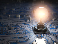 Glowing light bulb as CPU on motherboard circuit board. Idea creativity business concept.