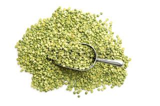 Green split peas in metal scoop.